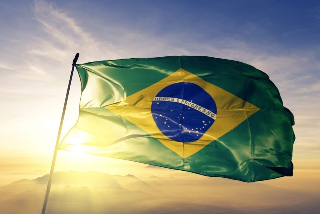 Brazil Brazilian flag waving with a sunrise in the background.