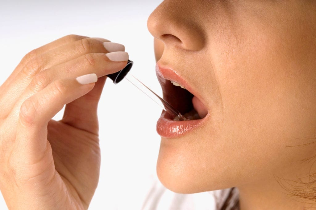 Extreme close-up of a young woman taking sublingual CBD.