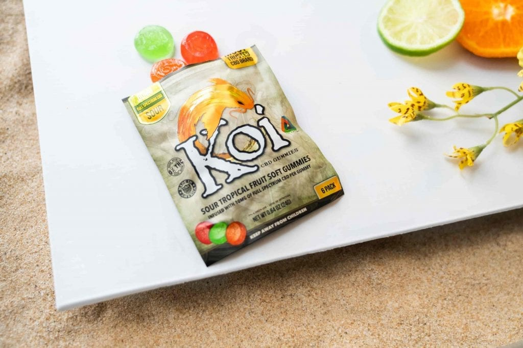 Bag of Koi Gummies on a tab;e with a few spilled out.