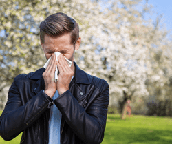 A man blowing his nose with a tissue.