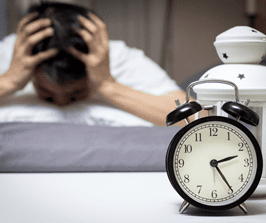 A man having trouble sleeping with his harms on his head while an alarm clock sits nearby.