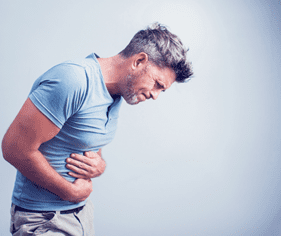 A man crunched over in stomach pain from IBS.