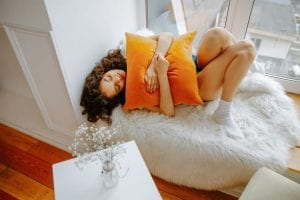 a woman holding a pillow while lying on her bed to help her cramps