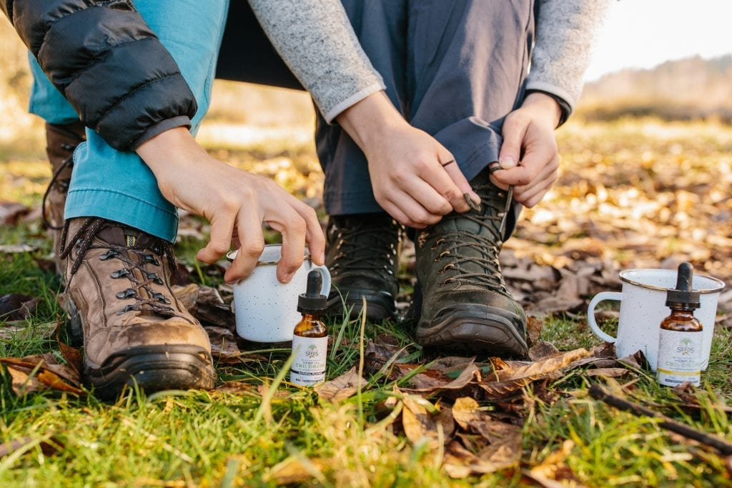 two hikers ready to start their morning with CBD oils and tinctures in their coffee