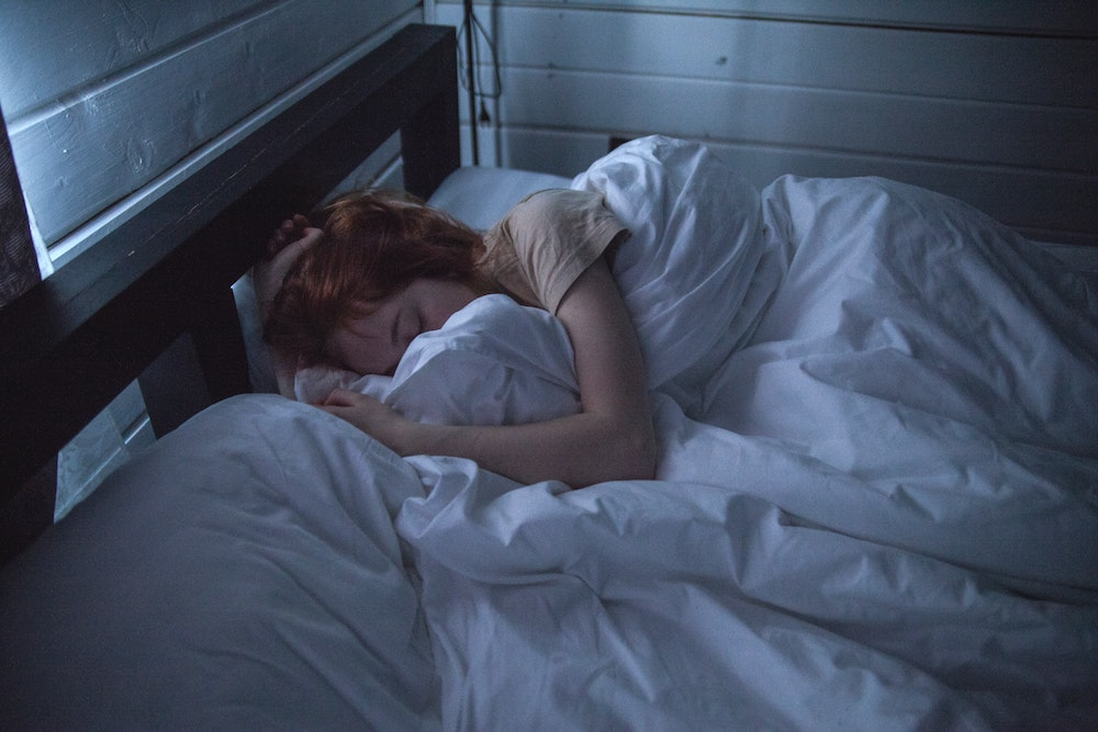 Woman sleeping in bed after taking cbd and melatonin