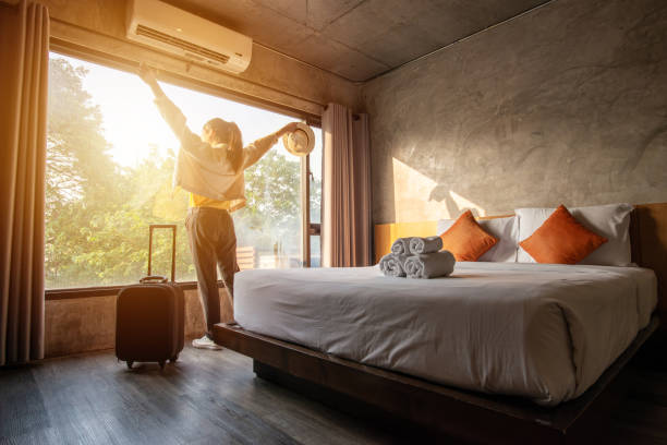 girl standing at window arms raised with luggage next to her in her hotel room next to her bed