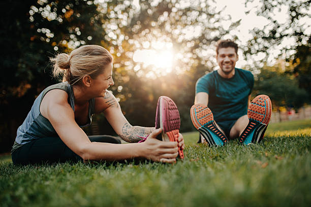 Fitness couple stretching outdoors in park. Young man and woman exercising together in morning.