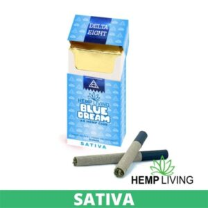 Blue cigarette box with white and blue writing - Blue Dream - Sativa from Hemp Living USA, 2 crossed dark-colored cigarettes laying in front right, with Hemp Living logo. green banner that says sativa on it at the bottom.