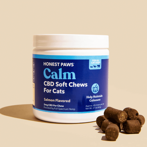 An Honest Paws Calm CBD Soft Chews for Cats white container with a blue label. Salmon Flavored. Brown, circular chews in front on the right hand side of container.